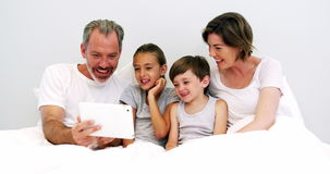 Family using digital tablet in bedroom. Happy family using digital tablet in bedroom at home stock video footage