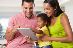 Family Using Digital Tablet In Kitchen Together Stock Image