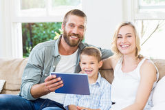 Family using digital tablet in living room Royalty Free Stock Photography