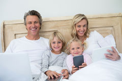 Family using digital tablet, mobile phone and laptop on bed in the bed room Royalty Free Stock Image
