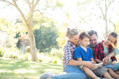 Family using digital tablet in the park Stock Photo