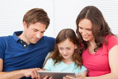 Family using digital tablet on sofa Stock Image