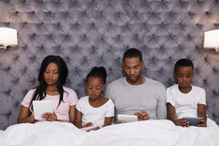 Family using digital tablets while sitting together on bed Royalty Free Stock Images