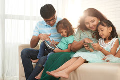 Family using gadgets Stock Images