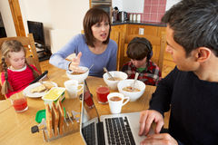Family Using Gadgets Whilst Eating Breakfast. Together In Kitchen Royalty Free Stock Photo