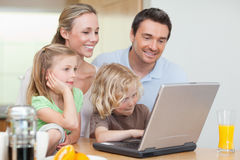 Family using the internet in the kitchen Stock Image