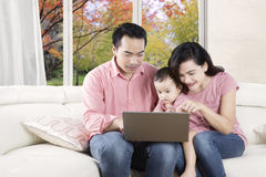 Family using a laptop with autumn background Royalty Free Stock Images