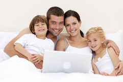 Family using a laptop in bed Royalty Free Stock Photo