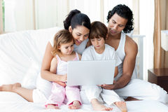 Family using a laptop on the bed Royalty Free Stock Images
