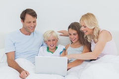 Family using a laptop. In bed Royalty Free Stock Images