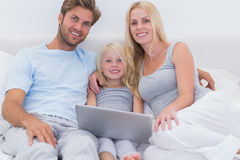 Family using a laptop in bed Royalty Free Stock Images