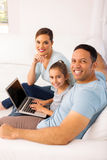 Family using laptop computer. Happy family of three using laptop computer while relaxing on sofa at home Royalty Free Stock Photos
