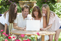 Family Using Laptop Computer Outside in Garden. An attractive happy, smiling family of mother, father and two daughters sitting using a laptop computer outside Stock Images