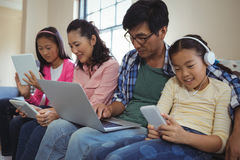 Family using laptop, digital tablet and mobile phone in living room Royalty Free Stock Photos