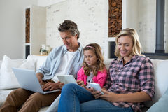 Family using laptop, digital tablet and mobile phone in living room Stock Images