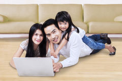 Family using laptop on the floor. Happy Asian family using a laptop computer while lying on the floor at home and smiling at the camera Stock Photo