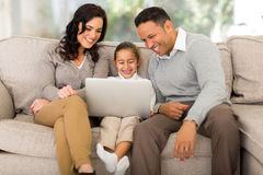 Family using laptop. Happy family using laptop in living room Royalty Free Stock Image