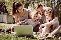 Family using laptop. Happy family using laptop, sitting on the  grass Stock Image
