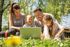 Family using laptop. Happy family using laptop, sitting on the green grass Stock Images