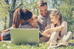 Family using laptop. Happy family using laptop, sitting on the green grass Stock Photo