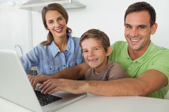 Family using a laptop in the kitchen Royalty Free Stock Images