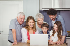 Family using laptop in kitchen. Family looking into laptop on table in kitchen at home stock image