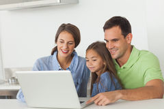 Family using a laptop on the kitchen table Royalty Free Stock Photo