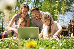 Family using laptop on the meadow. Happy family using laptop, sitting on the green grass Royalty Free Stock Photos