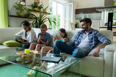 Family using laptop and mobile phone in living room Stock Photos