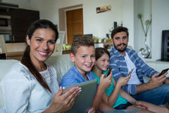 Family using laptop and mobile phone in living room at home Stock Photo