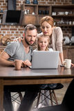 Family using laptop. Pensive young family using laptop together in kitchen Stock Image
