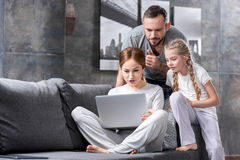 Family using laptop. Pensive young family using laptop together on sofa Royalty Free Stock Photo