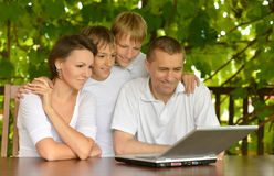Family using laptop. Portrait of a family using laptop together outdoors Royalty Free Stock Images
