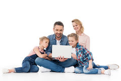 Family using laptop while sitting on floor isolated on white. Smiling family using laptop while sitting on floor isolated on white royalty free stock image