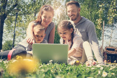 Family using laptop, sitting on the green grass. Family en. Happy family using laptop, sitting on the green grass. Family enjoying on the meadow in the spring Royalty Free Stock Photos
