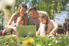 Family using laptop, sitting on the green grass. Family en. Happy family using laptop, sitting on the green grass. Family enjoying on the meadow in the spring Royalty Free Stock Photography