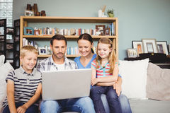 Family using laptop while sitting on sofa. Happy family using laptop while sitting on sofa at home Stock Photography