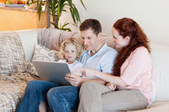 Family using laptop on the sofa Stock Image