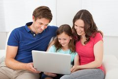 Family using laptop on sofa Stock Photos