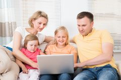 Family using laptop on sofa Royalty Free Stock Photos