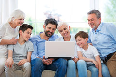 Family using laptop on a sofa Royalty Free Stock Images