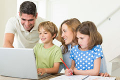 Family using laptop at table Royalty Free Stock Image