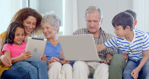 Family using laptop and tablet. On couch stock footage