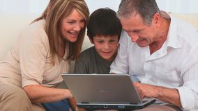 Family using a laptop to play a game stock video footage