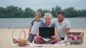 Family using laptop to talk to grandmom stock video footage