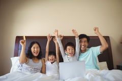 Family using laptop together in bedroom Stock Photography