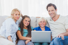 Family using a laptop together. Sitting on a couch Stock Images