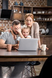 Family using laptop. Young family using laptop and drinking tea or coffee in kitchen Royalty Free Stock Photography