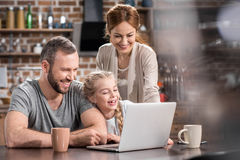 Family using laptop. Young family using laptop in kitchen and laughing Royalty Free Stock Images