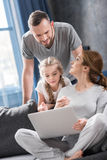 Family using laptop. Young family using laptop together at home Royalty Free Stock Photos